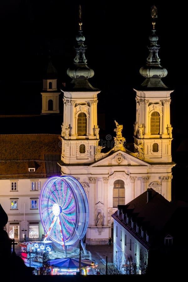 Graz con la chiesa Mariahilf e natale giusto con la ruota di ferris fotografia stock