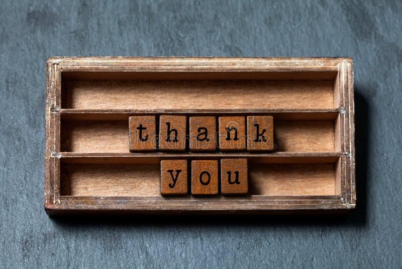 Grazie concetto Scatola d'annata, frase di legno dei cubi con le lettere di vecchio stile Fondo strutturato della pietra grigia P fotografie stock