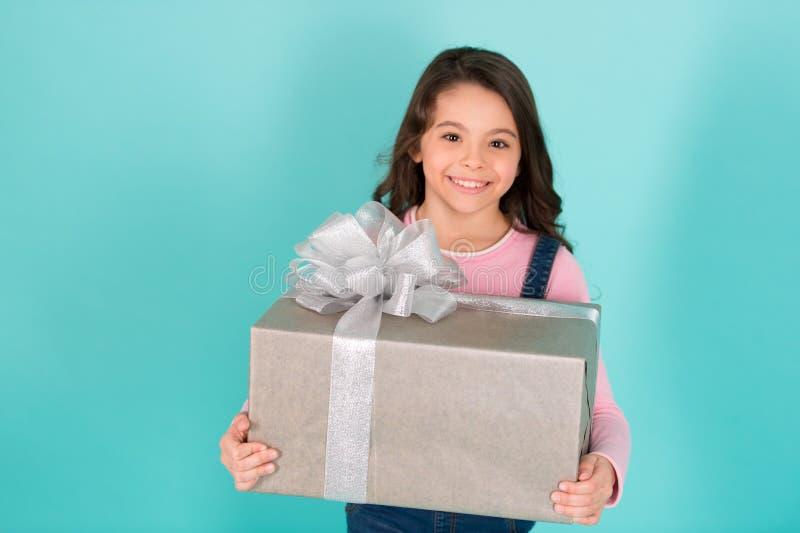 Grazie mille Il fronte felice del bambino tiene il grande fondo del turchese del contenitore di regalo Regalo contentissimo della fotografia stock