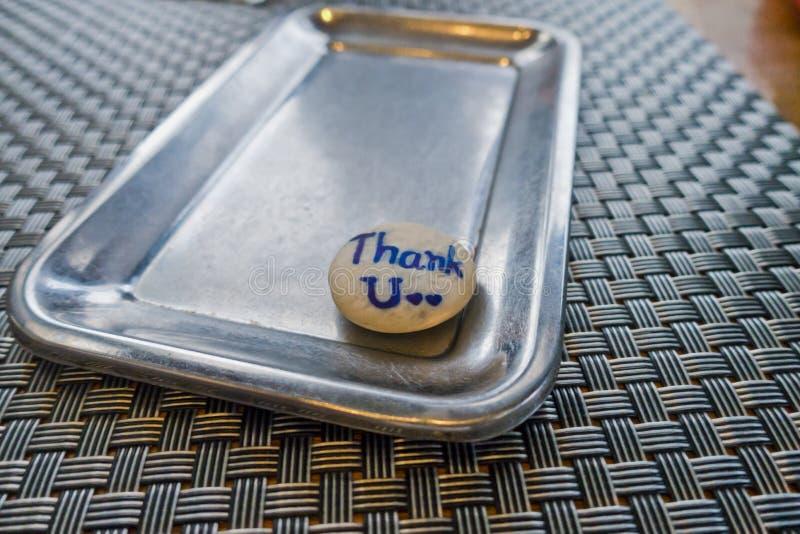 Grazie parole su una pietra su un vassoio e su una tavola - fondo fotografia stock libera da diritti