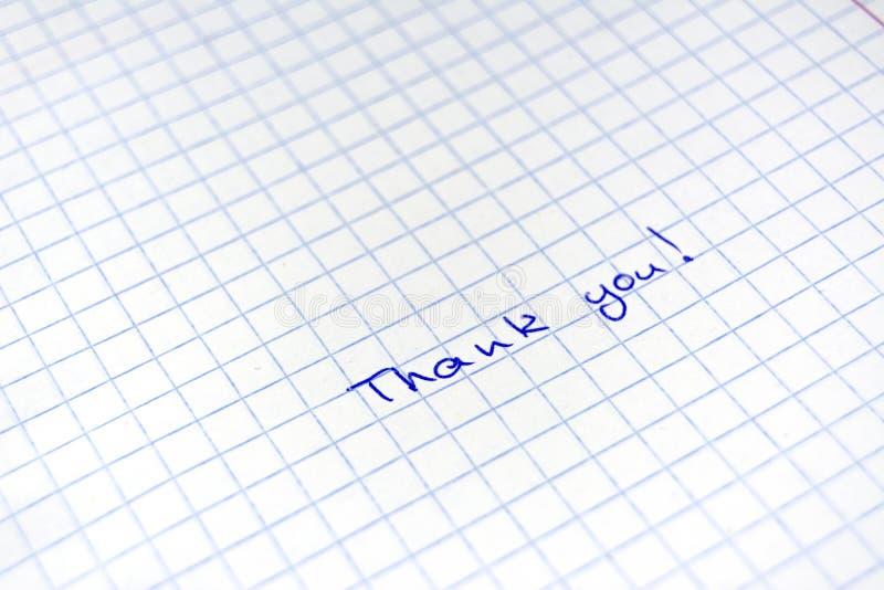 Grazie scritti a mano dell'iscrizione alla penna blu su uno strato in una gabbia fotografie stock libere da diritti