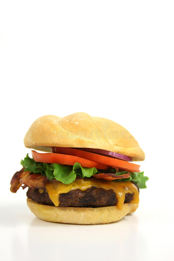 Greasy cheeseburger. Over white with cheese bacon lettuce tomato,shallow dof royalty free stock photos