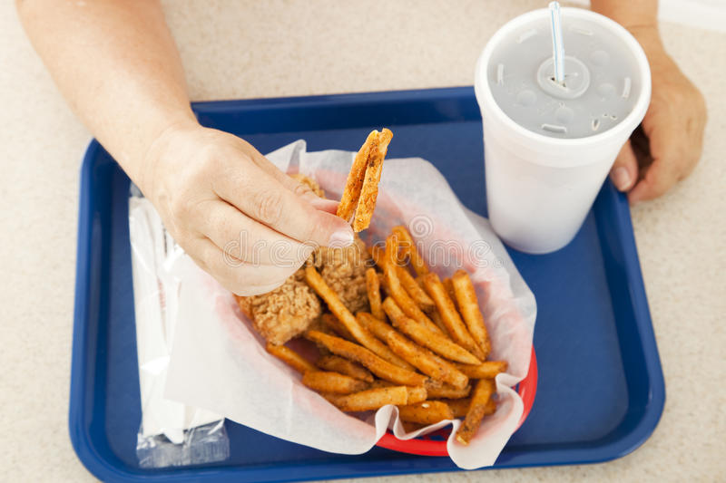 Greasy French Fries. A plate of greasy fast food, with the customer holding up a greasy french fried potato to the camera. Focus on the hand and the fry stock photography