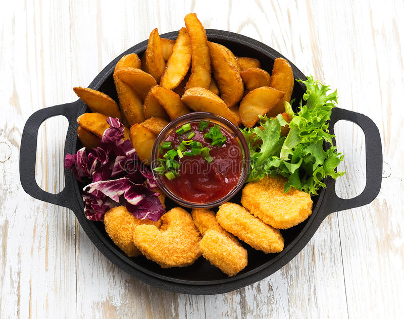 Greasy fried chicken, french fries, ketchup and salad. stock photo