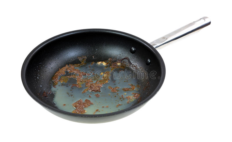 Greasy frying pan. A frying pan with the greasy residue of fried hamburger on a white background royalty free stock photography