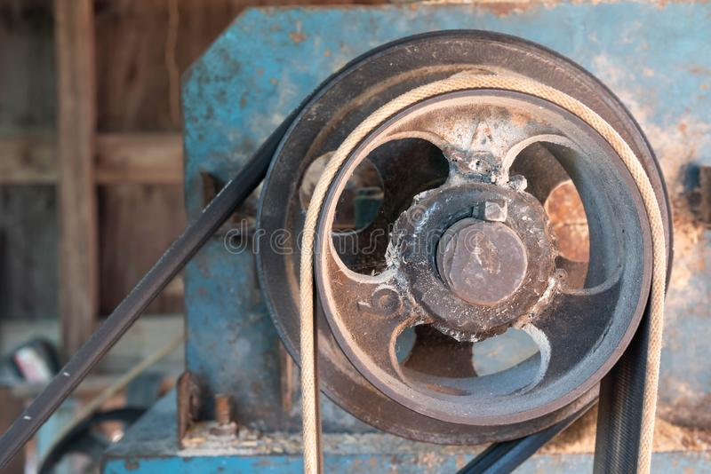 Greasy oil and dust are attached to the pulley. Old machine with belt industry industrial equipment vintage gear press detail antique ancient iron production stock images