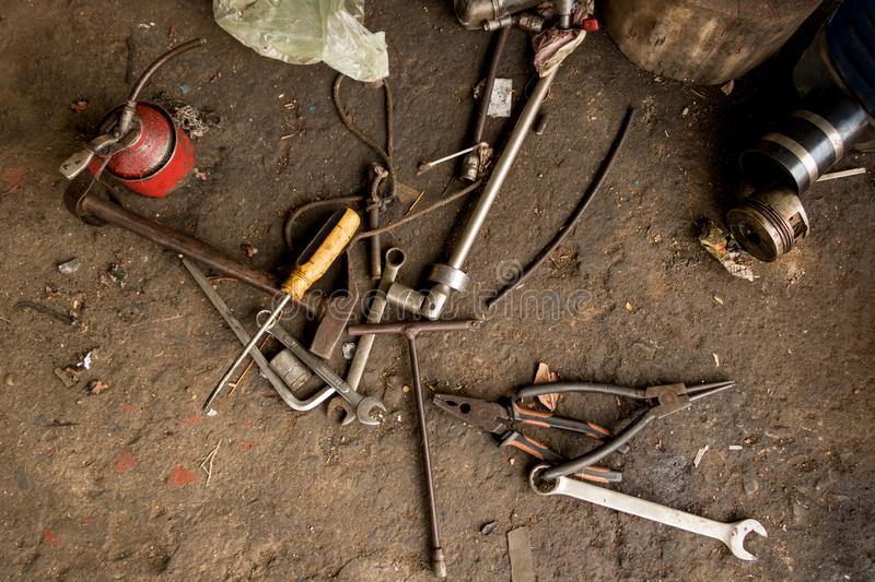 Dirty Tools on Oily Concrete Ground - Construction Equipment. Greasy Tools on Dirty Concrete Floor. Messy Garage stock image