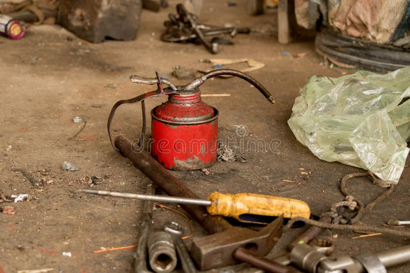 Vintage Red Lubricant Oil Can with Greasy Tools on Dirty Concrete Ground. Greasy Tools on Dirty Concrete Floor. Messy Garage royalty free stock image