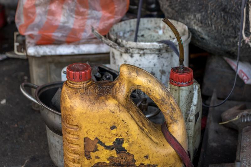 Dirty Old Diesel Bottle/ Oil Can in Greasy Garage - no Label. Greasy Tools on Dirty Ground stock photos