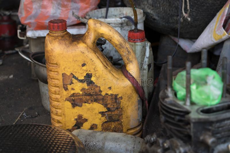 Empty Old Plastic Container/ Greasy Diesel Bottle/ Dirty Lubricant Oil Can with Peeled Label- Messy Garage with Tools and Broken. Greasy Tools on Dirty Ground royalty free stock photos