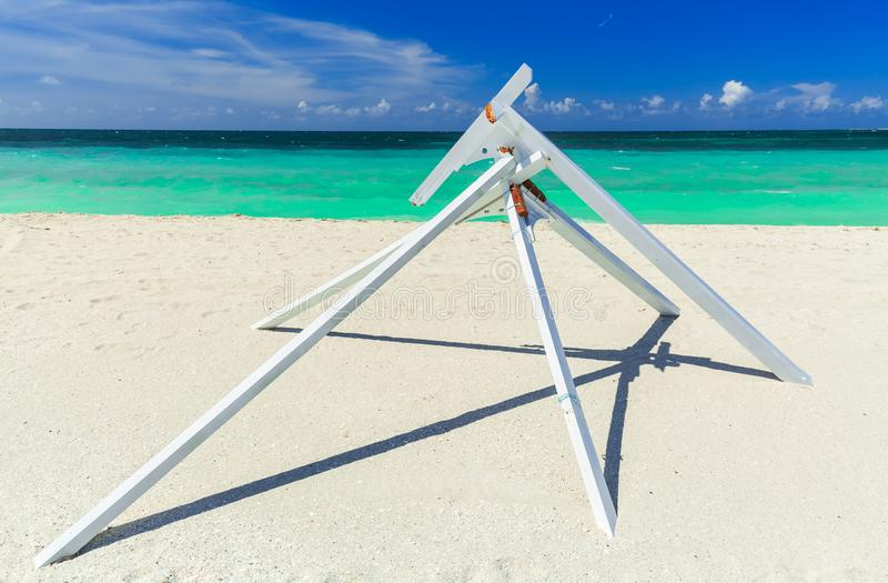 Amazing abstract wooden structure standing at Varadero Cuban beach against dark blue sky and tranquil turquoise ocean background stock images