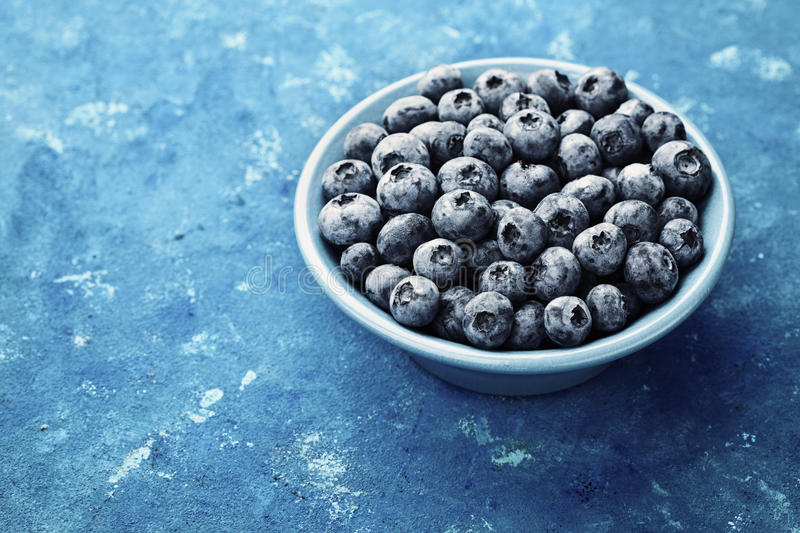 Great bilberry or blueberry in plate on blue rustic background. Vintage style. royalty free stock photos