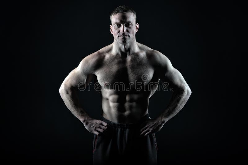 Great body result of regular training gym. Man muscular torso body posing confidently black background, copy space. Bodybuilder achievement great shape stock photos