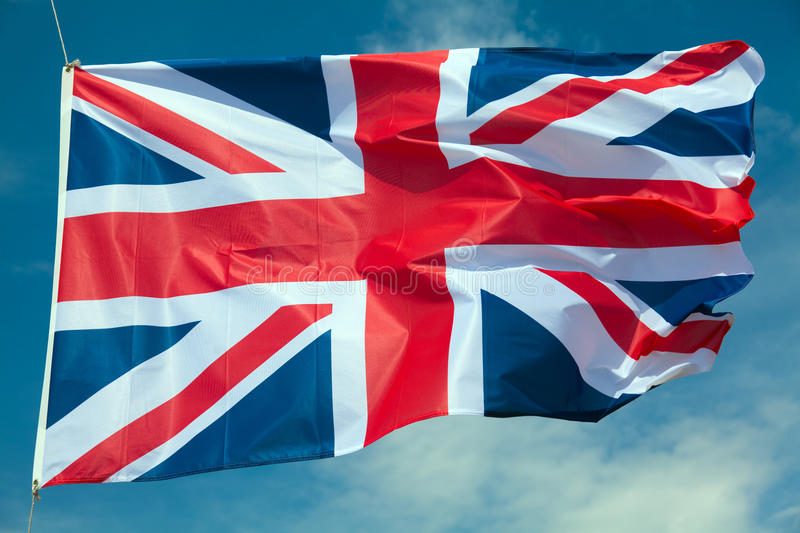 Great Britain flag. Against blue sky stock image