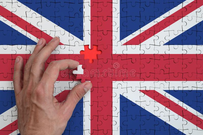 Great britain flag is depicted on a puzzle, which the man`s hand completes to fold stock photos