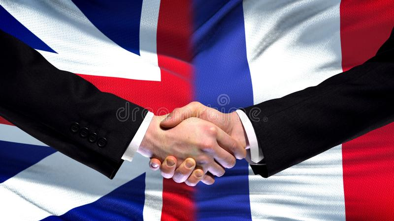Great Britain and France handshake, international friendship, flag background royalty free stock photos
