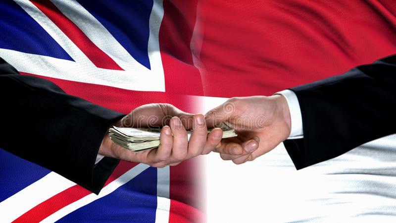 Great Britain and Indonesia officials exchanging money, flag background, deal royalty free stock images