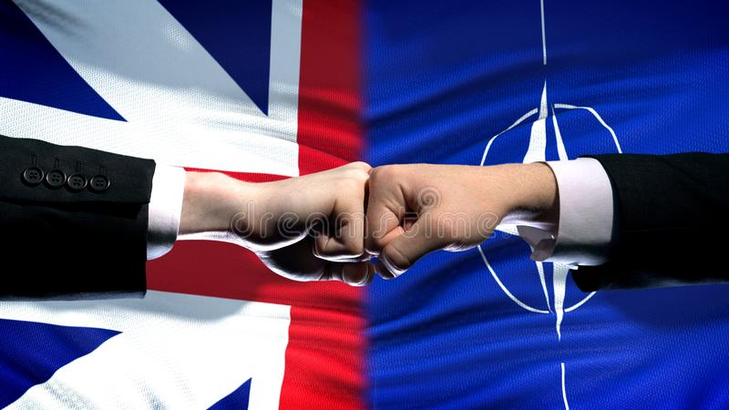Great Britain vs NATO conflict, fists on flag background, diplomatic crisis stock images