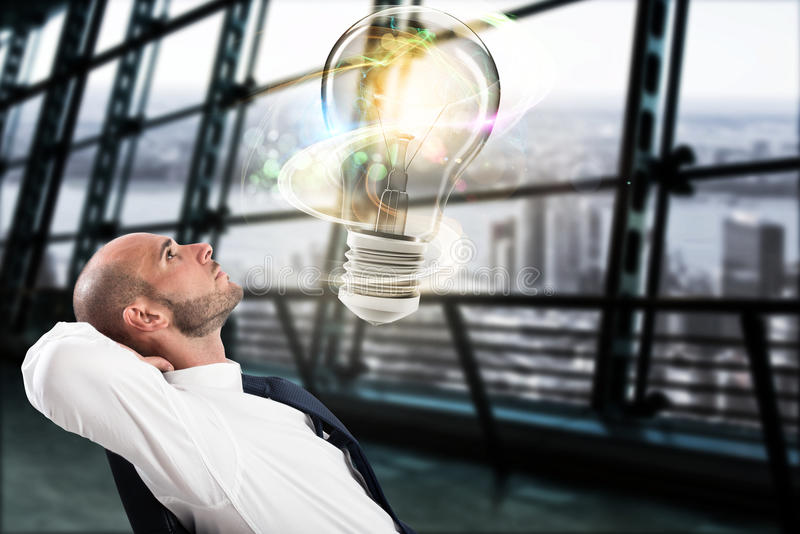Great business idea concept. Businessman looks a big light bulb in his office. Great business idea concept royalty free stock photo