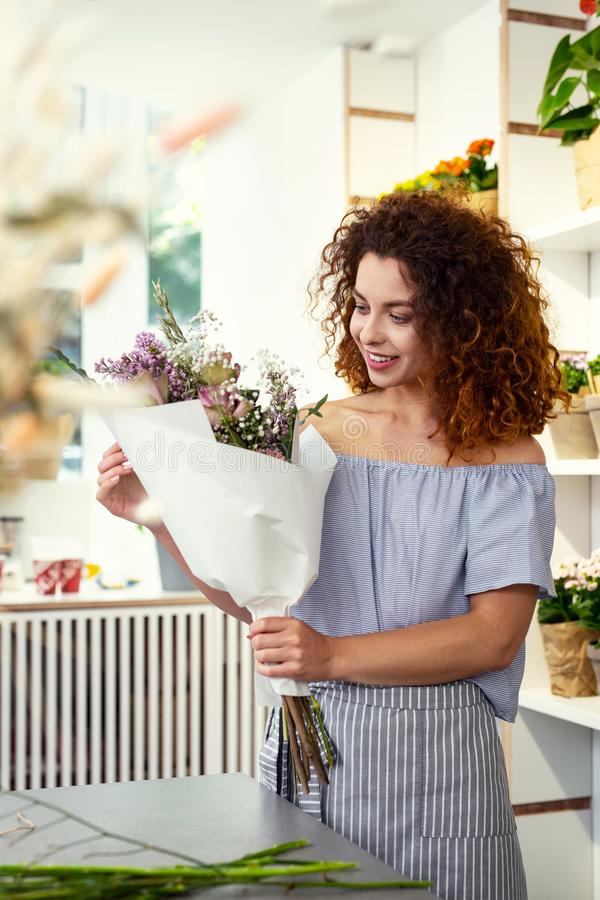 Positive attractive woman standing in the flower shop royalty free stock photos