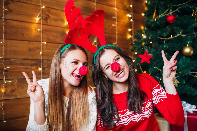 Female friends winking and laughing NEAR Christmas tree stock images