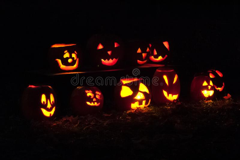 Spooky collection of Jock O` Lanterns on a crisp fall evening stock images