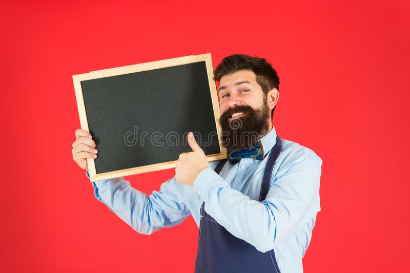 Great cuisine. cooking by recipe. bearded hipster cook in apron. happy man chef with blank blackboard, copy space. Welcome. Restaurant or cafe advertising stock image