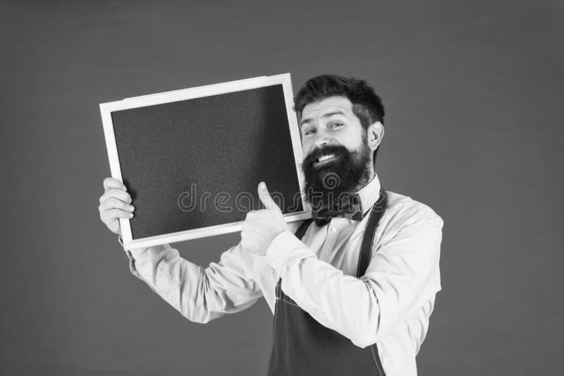 Great cuisine. cooking by recipe. bearded hipster cook in apron. happy man chef with blank blackboard, copy space. Welcome. Restaurant or cafe advertising royalty free stock images