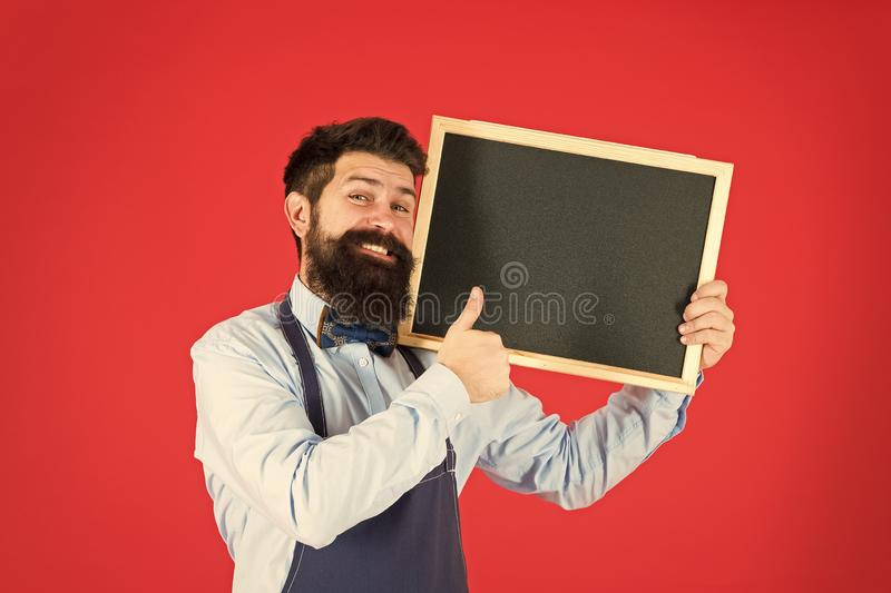 Great cuisine. cooking by recipe. bearded hipster cook in apron. happy man chef with blank blackboard, copy space. Welcome. Restaurant or cafe advertising stock photography