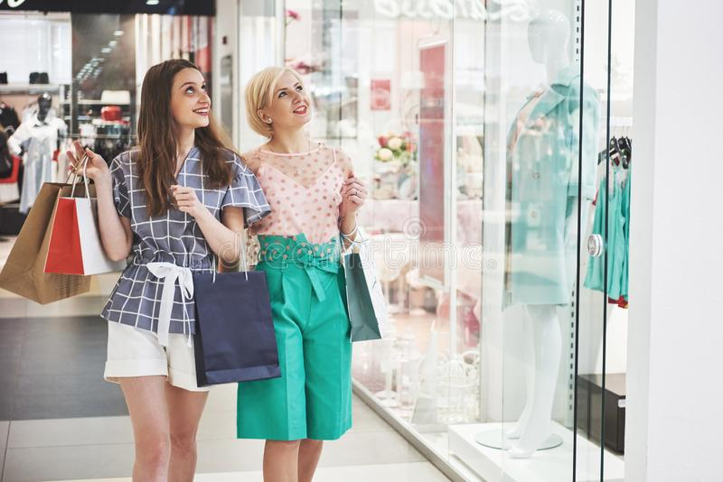 Great day for shopping. Two beautiful women with shopping bags looking at each other with smile while walking at the royalty free stock image