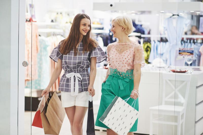 Great day for shopping. Two beautiful women with shopping bags looking at each other with smile while walking at the stock images