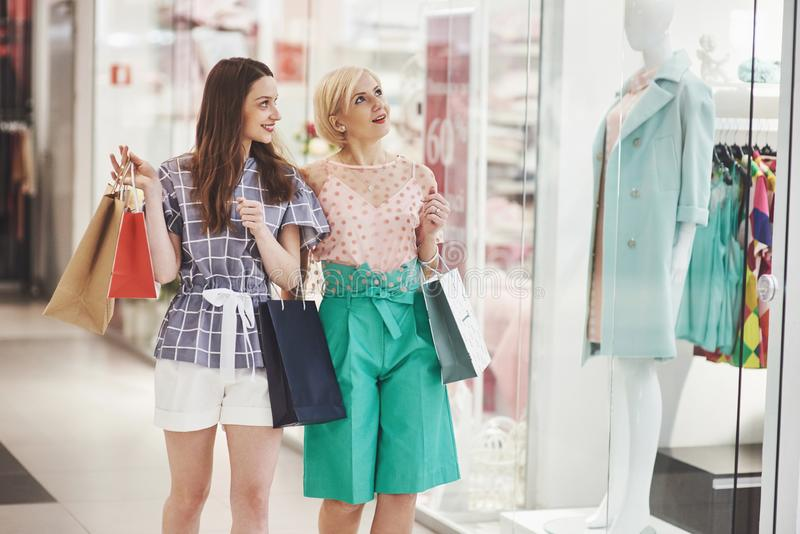 Great day for shopping. Two beautiful women with shopping bags looking at each other with smile while walking at the royalty free stock images