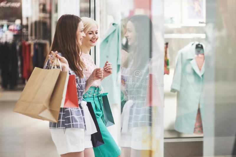 Great day for shopping. Two beautiful women with shopping bags looking at each other with smile while walking at the stock image