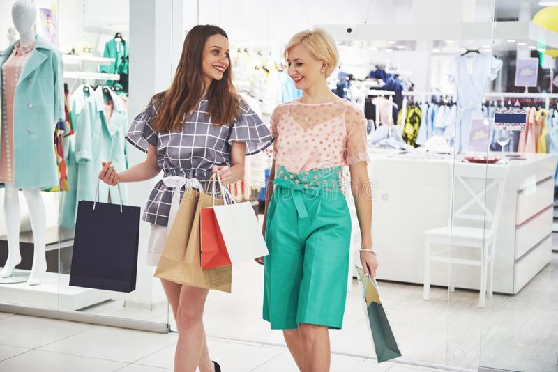 Great day for shopping. Two beautiful women with shopping bags looking at each other with smile while walking at the royalty free stock photo