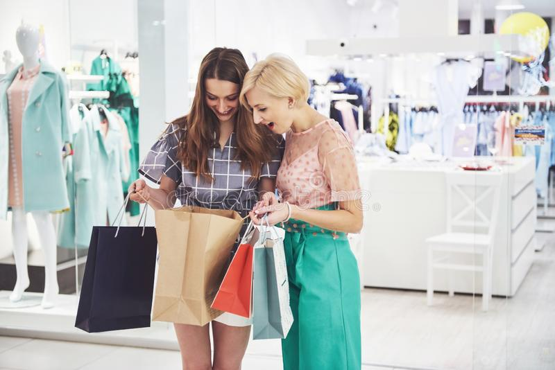 Great day for shopping. Two beautiful women with shopping bags looking at each other with smile while walking at the stock photo