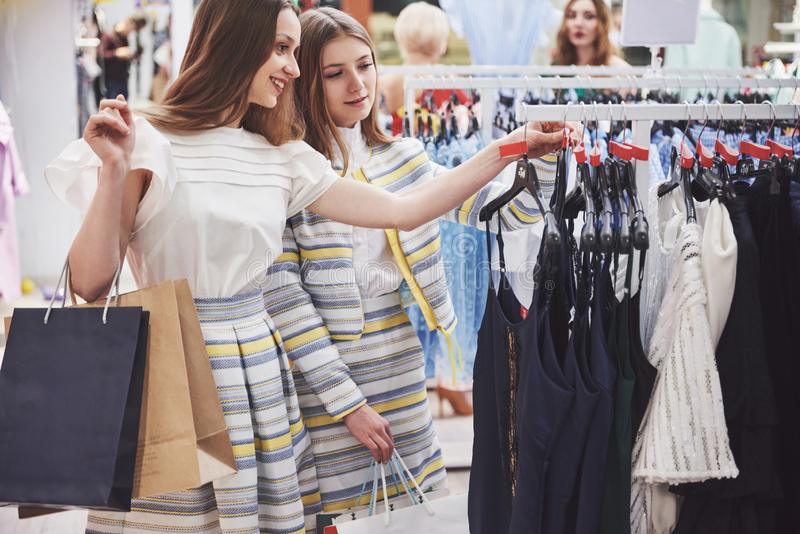 Great day for shopping. Two beautiful women with shopping bags looking at each other with smile while walking at the stock photos