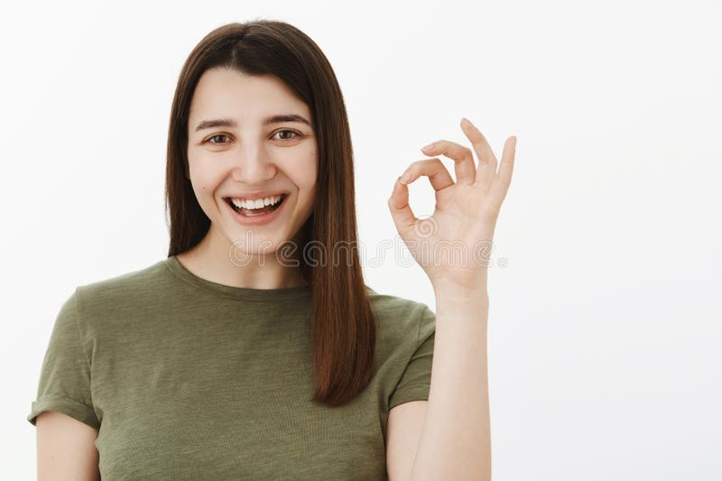 Great deal, confirm it. Happy and carefree optimistic european brunette in olive t-shirt showing okay sign and smiling royalty free stock photography
