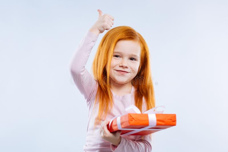 Delighted cute girl enjoying her birthday present royalty free stock photo