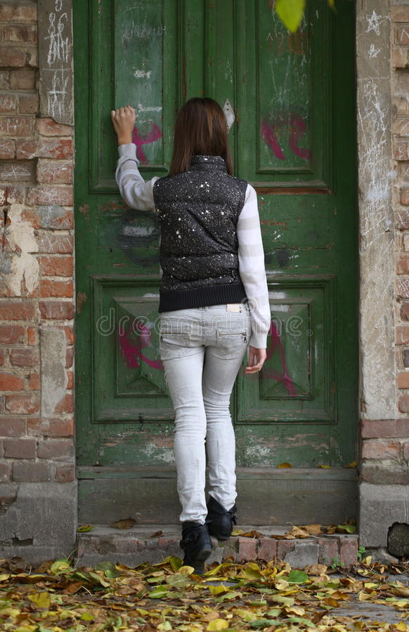 Great Expectations. Teenager girl knocking at the old door royalty free stock photography