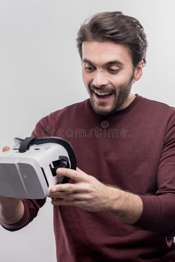 Great fan of video games holding virtual reality glasses in hands. Fan of games. Great fan of video games holding virtual reality glasses in hands on image stock image