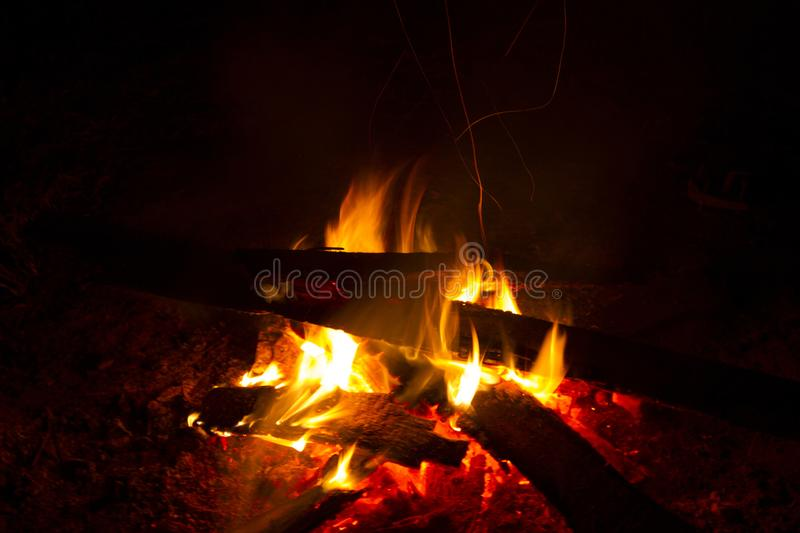 Great fire burns in the night. Many wooden planks are stacked together and a fire is burning. The time and place of the action - street, night, village stock images