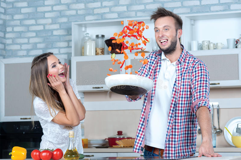 Great fun on the kitchen. Couple in love is cooking on the kitchen stock images