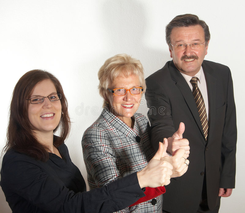 Great future. Small group of business people in business suits showing thumbs up. Focus is on the young woman in front royalty free stock photography