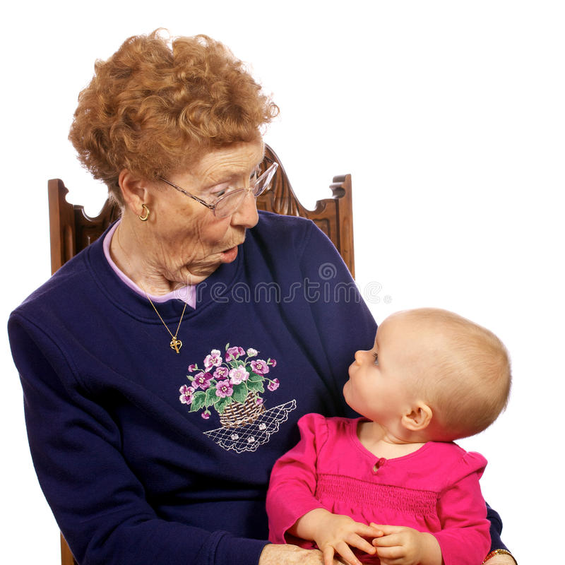 Great Grandma with Grand baby enjoying each other. Great grandmother holding grand baby as they entertain each other stock images
