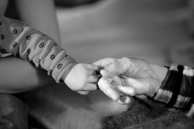 Great-grandmother and baby hands close up royalty free stock images
