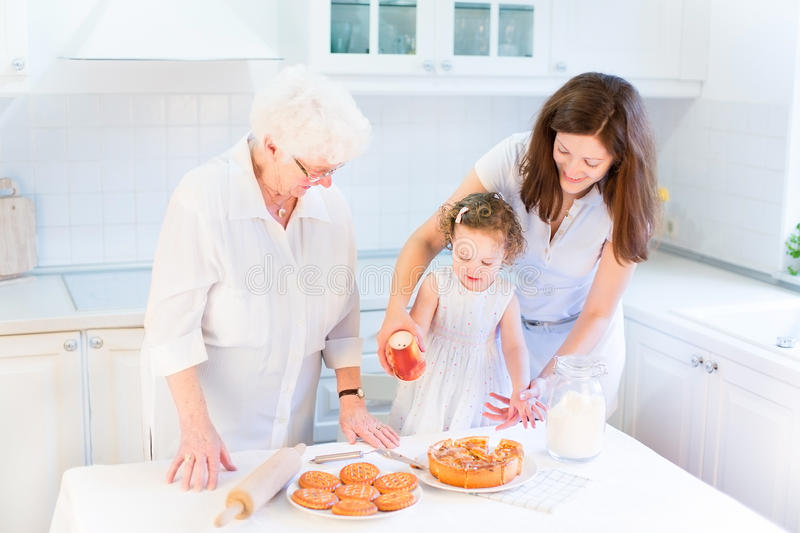 Great grandmother baking apple pie with her family stock photos