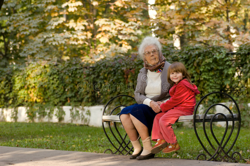 Great grandmother and child. Sitting on the bench in the park holding hands stock image