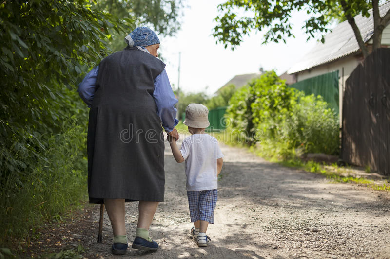 Great grandmother and toddler boy holding hands while walking down street stock image