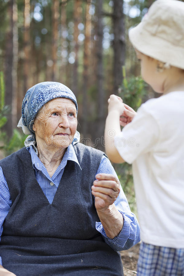Great grandmother and toddler boy talking during walk. In park or forest royalty free stock photos