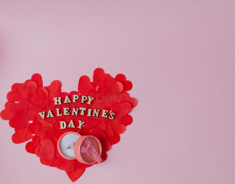 A great heart of small paper hearts and a wedding ring on a pink background with an inscription Happy Valentine`s Day.  stock images
